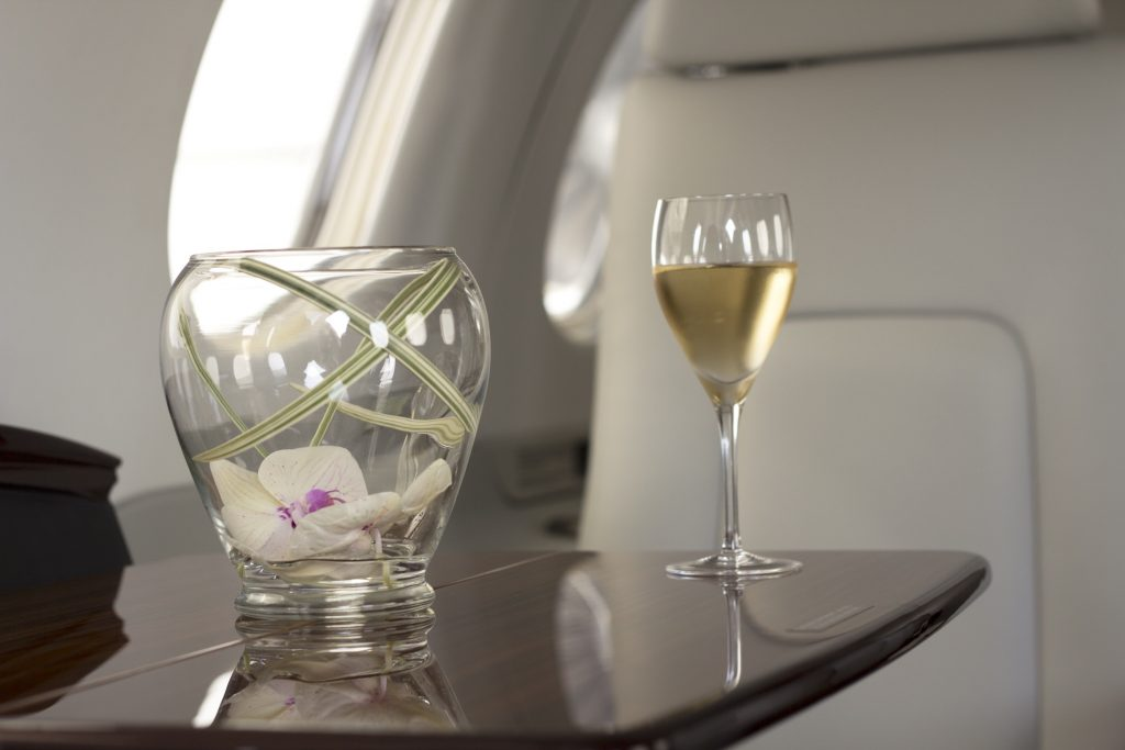 Private Jet to Van Nuys with wine glass and flower vase on private jet table