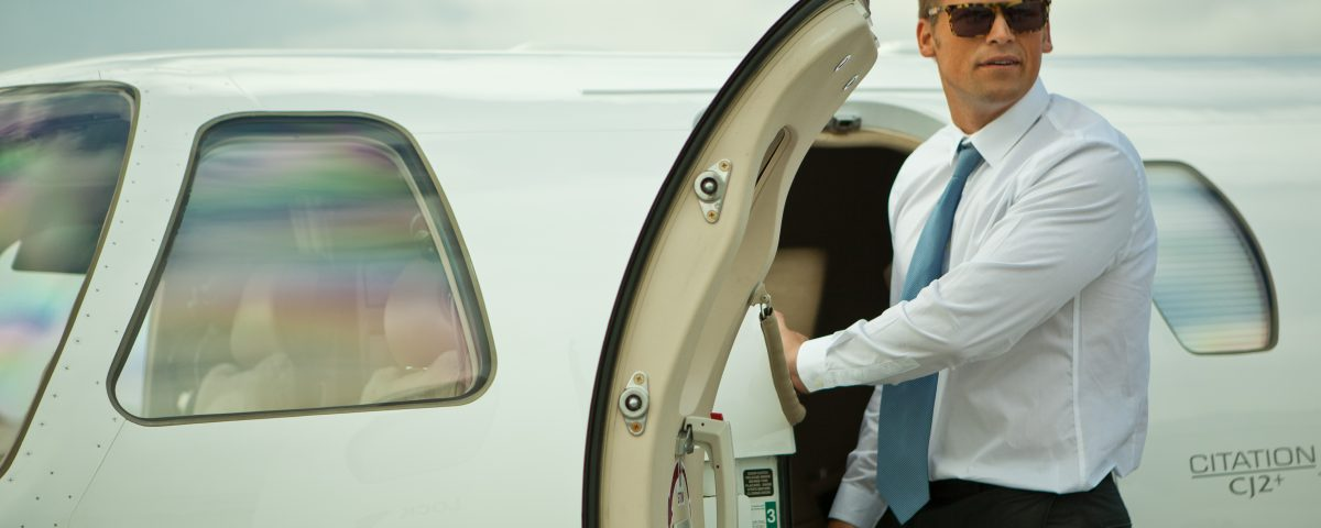 Business man stepping out of private corporate jet
