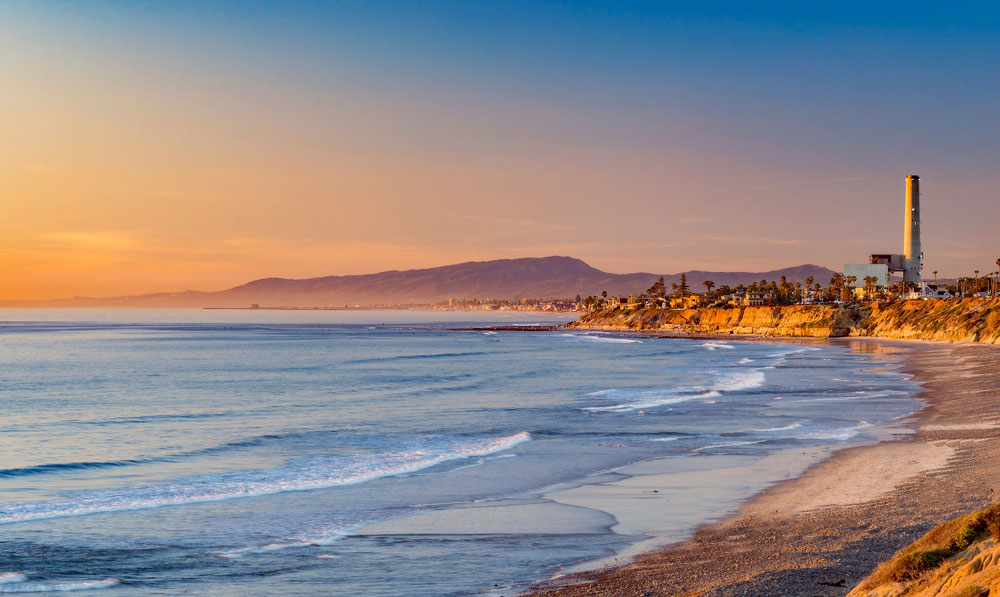 Private Jet to Carlsbad to see the beach shoreline and orange sunset with lighthouse