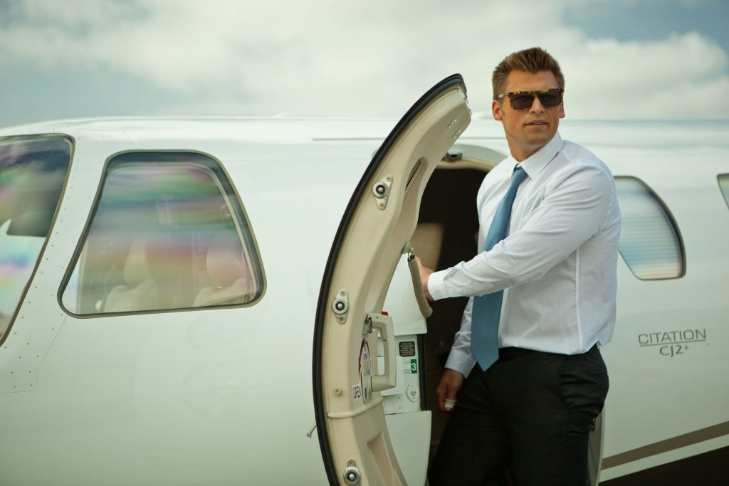 Man with sunglasses in suit getting on private jet to Monterey