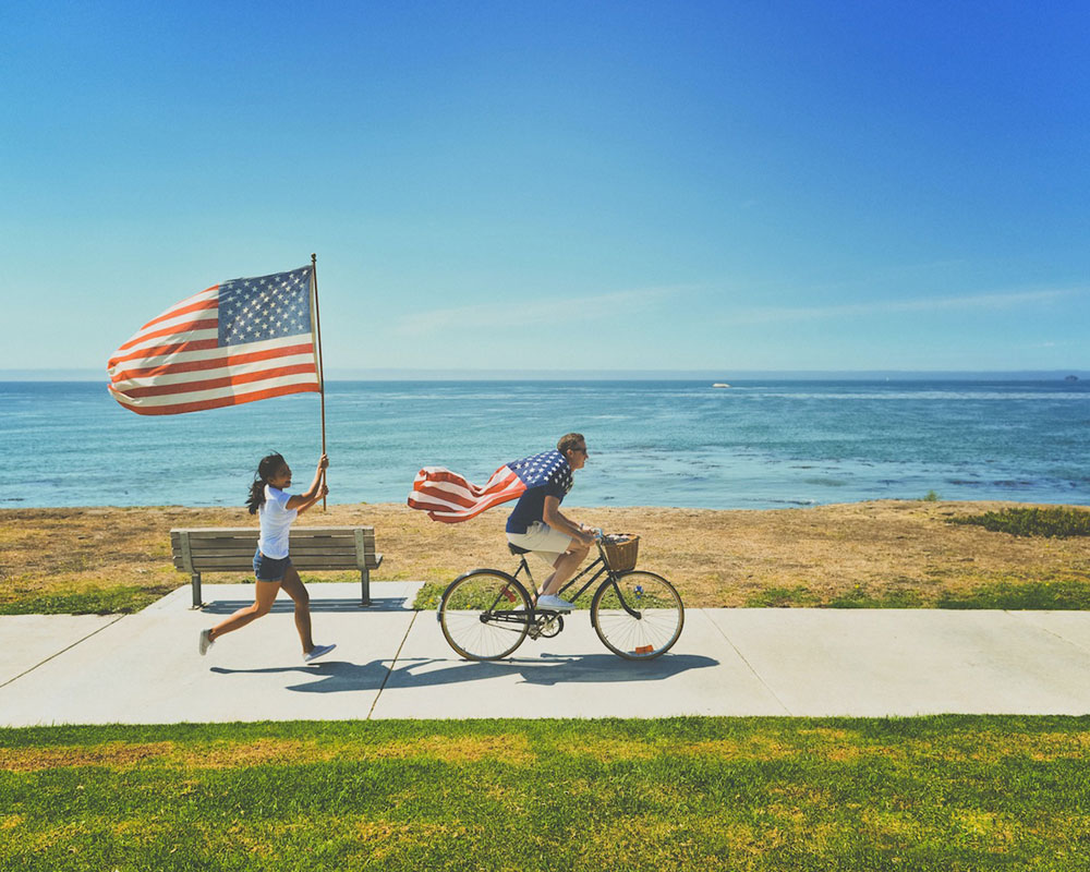 Things to do in California for Fourth of July - man and woman running and riding bikes at beach with American flags