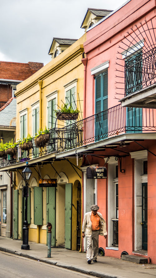 Take a private jet to see the colorful houses with man walking down New Orleans street