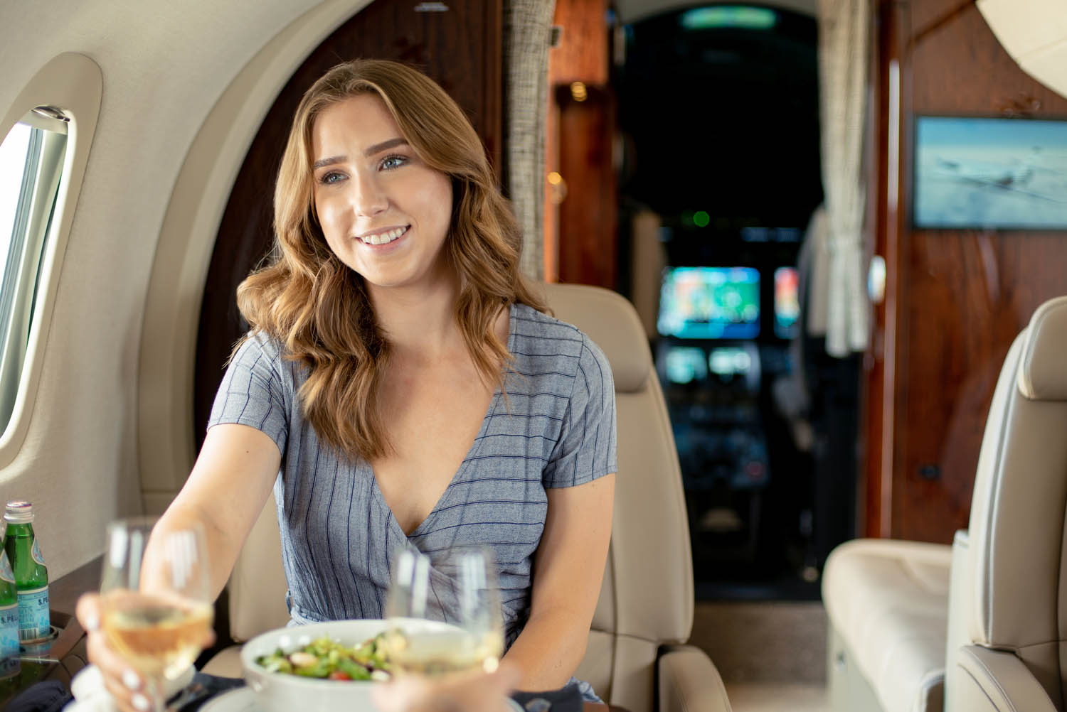 Girl on a private jet to Scottsdale with wine and salad