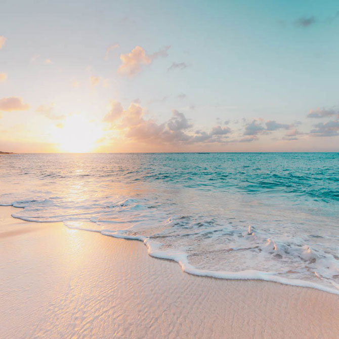 Private jet to Hawaii with white sand beaches and blue water and pink sunset