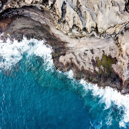 Private jet to an aerial view of Honolulu Hawaii's ocean and cliffs