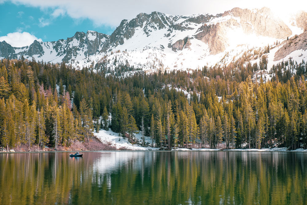 Private jet to Mammoth Lakes with snowy mountains and trees and a lake