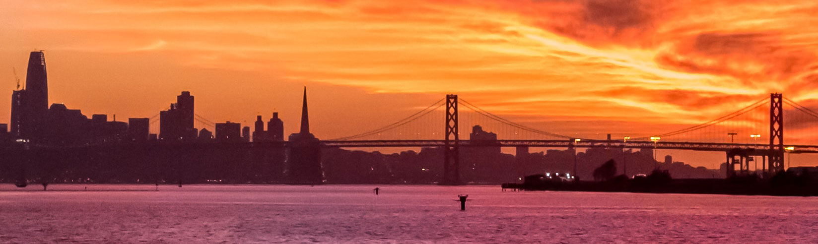 Private jet to Oakland with orange sunset over bay bridge