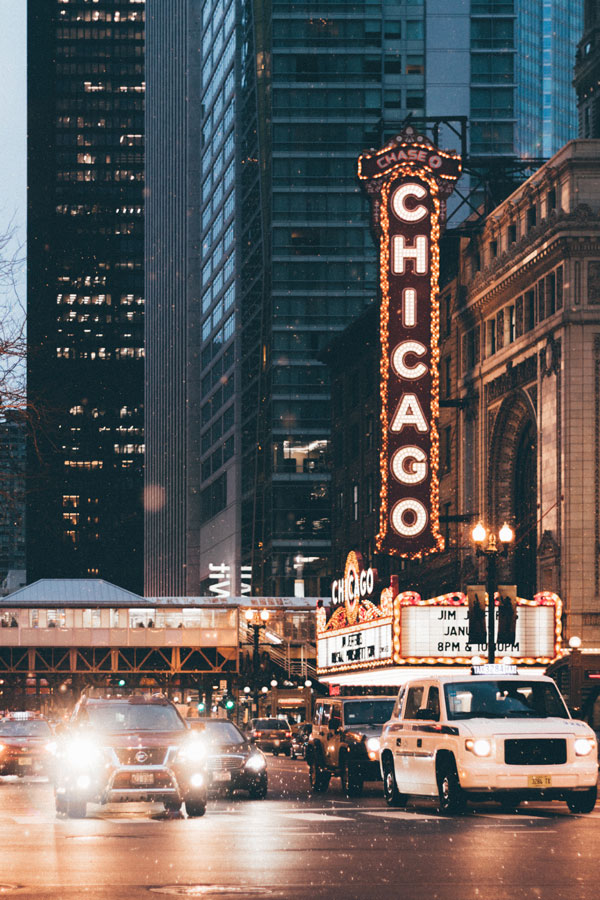 Private jet to Chicago with skyscrapers and night lights and cars driving on street with Chicago light sign