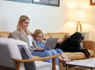 How to charter a private jet, mom, daughter, and dog sitting on couch booking a flight in a private jet