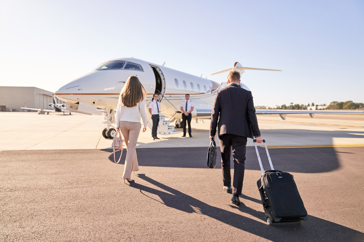 How to charter a private jet, business woman and man walking towards aircraft