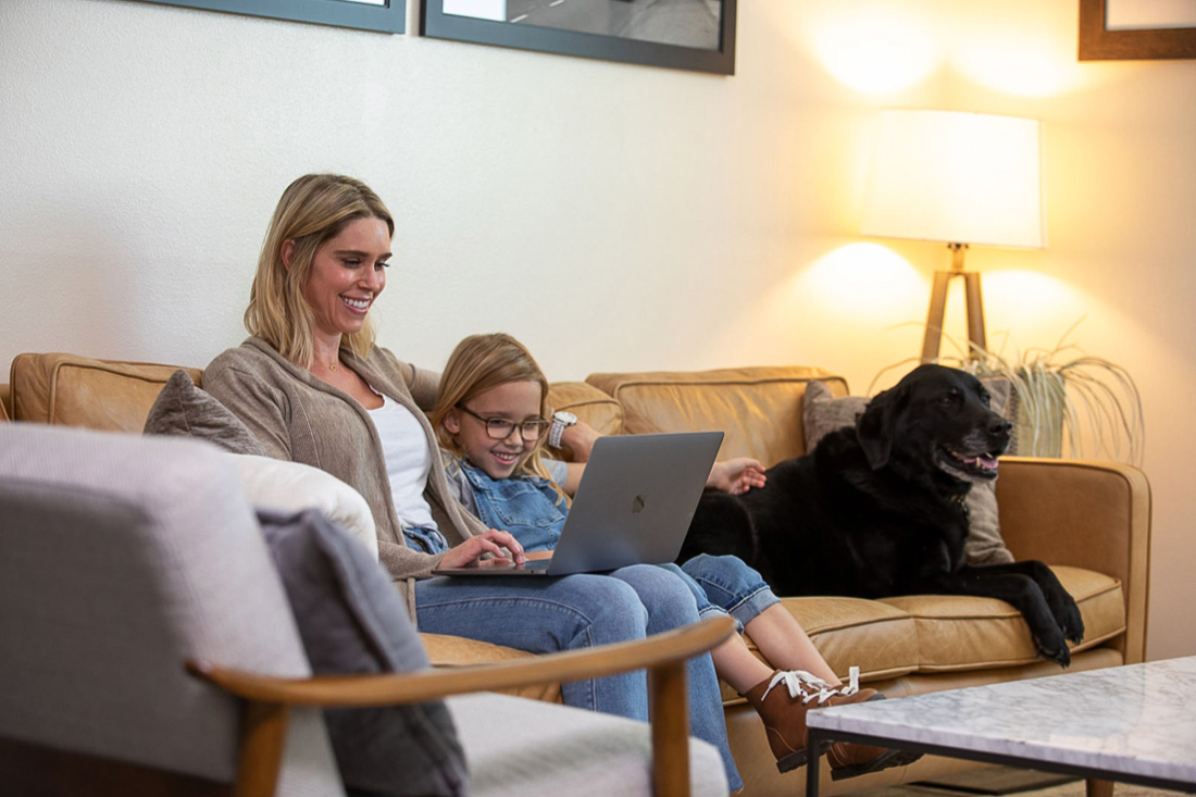 Top 5 Tips for Private Jet Travel this Summer with Latitude 33 Aviation - Mom, Daughter, and Dog booking a flight at home